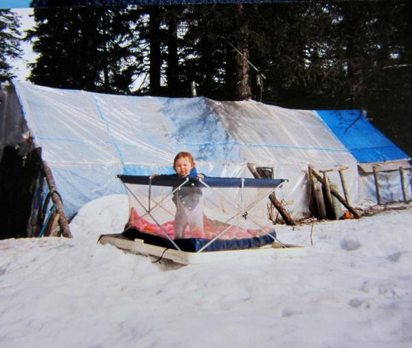 Detricia's daughter outside of their home: a plastic tent made of visqueen.