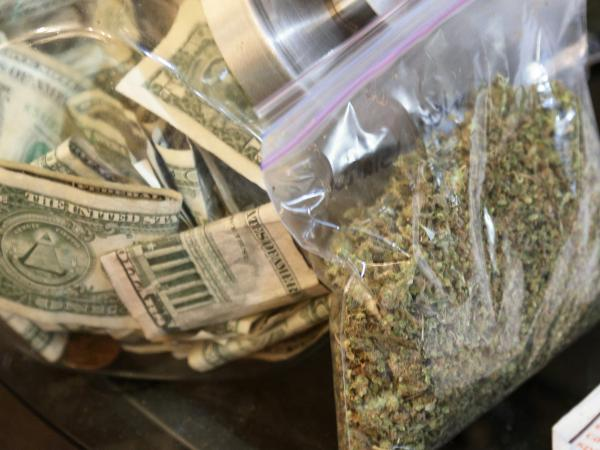 A bag of marijuana being prepared for sale sits next to a money jar at BotanaCare in Northglenn, Colorado, in this file photo taken on December 31, 2013.
