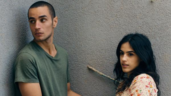Omar (Adam Bakri) is a Palestinian baker and secret informant who braves the wall that splits his community to visit his lover, Nadia (Leem Lubany) in the Oscar-nominated film <em>Omar. </em>