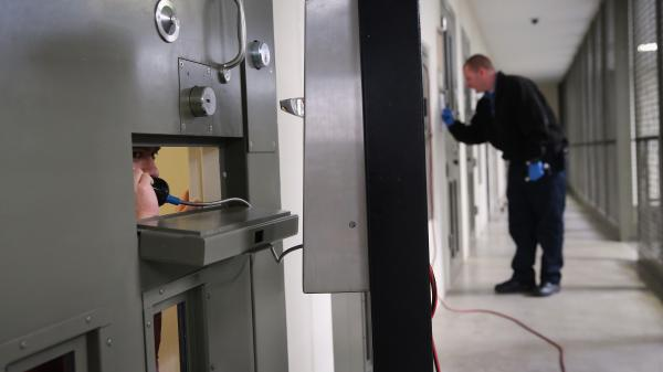"""The U.S. holds more prisoners in solitary confinement than any other democratic country, according to critics of the treatment. Here, an immigrant detainee makes a call from his """"segregation cell"""" at a detention facility in Adelanto, Calif., last November."""