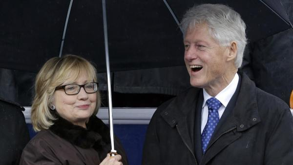 Former Secretary of State Hillary Rodham Clinton and former President Clinton huddle under an umbrella during inaugural ceremonies for Virginia Gov. Terry McAuliffe in Richmond on Jan. 11.
