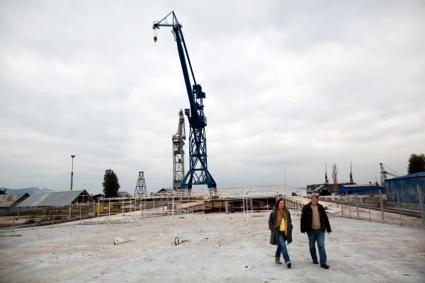 Alexandra Tsitoura (left) and Nikos Aivatzidis walk through now-empty Hellenic Shipyards in Athens, Greece. Two years ago, the shipyard employed around 1,100 workers. Alexandra and her husband Nikos have had jobs at Hellenic Shipyards for 10 and 31 years, respectively, but have not received neither a paycheck nor any form of severance for the past two years.