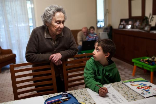 "Tsitoura's mother Maria, visiting from her home in Kalamata, helps Dimitris with homework. ""From an early age, the parents are saying, 'Study, study!' "" Tsitoura said. ""We want them [our children] to be somebody, but there are so few opportunities."""