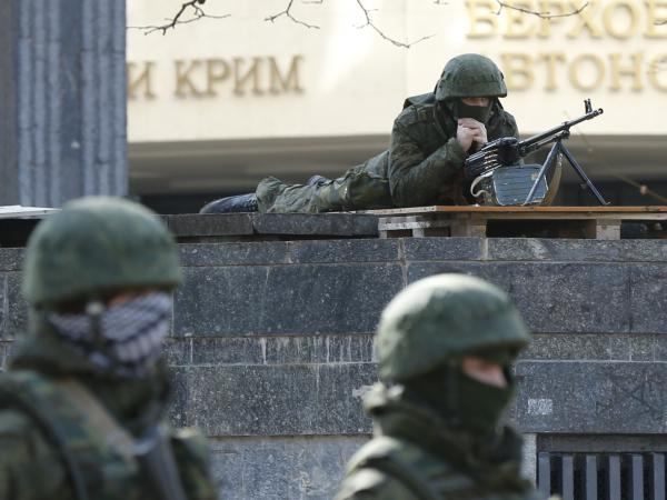 "Armed men take up positions around the regional parliament building in the Crimean city of Simferopol on Saturday. Ukraine's defense minister said on Saturday Russia had ""recently"" brought 6,000 additional personnel into Ukraine."