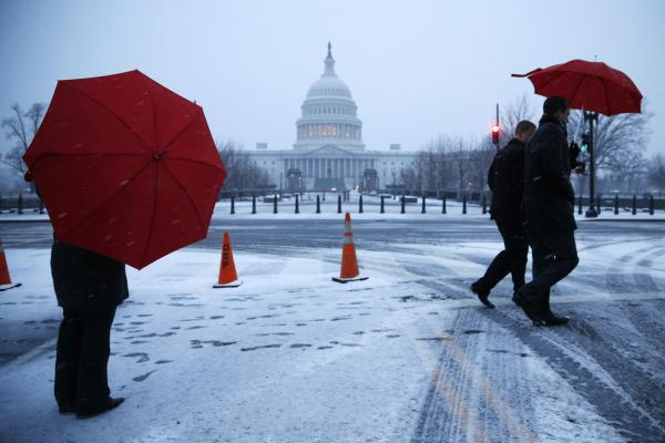 People walk through early morning snow near the Capitol in Washington, D.C.