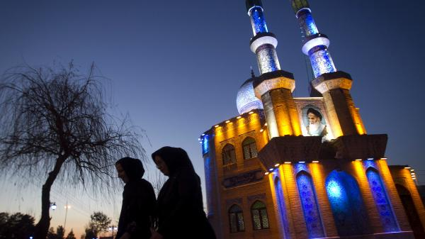 Two Iranian women walk past a mosque in the western city of Kermanshah, Iran, last month.