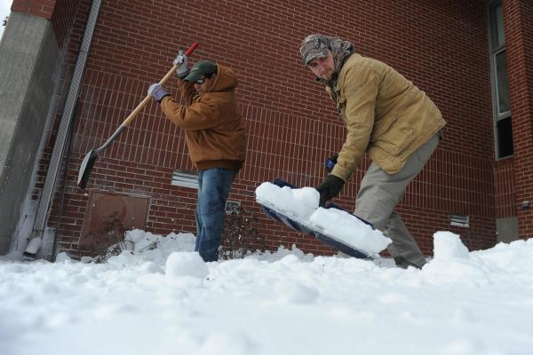 "Roberto Molina (left), and Austin Moore work to shovel snow in front of Clark Elementary in Paducah, Ky., on Monday. ""State highways officials say road crews are out this morning clearing roads, but warned that they are having a hard time keeping up with heavy snow, and told drivers to stay off the roads if possible,"" the <em>Charleston Gazette</em> in West Virginia reports."