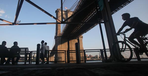 A cyclist rides beneath the Brooklyn Bridge during the evening commute August 25, 2009 in New York City. (Mario Tama/Getty Images)