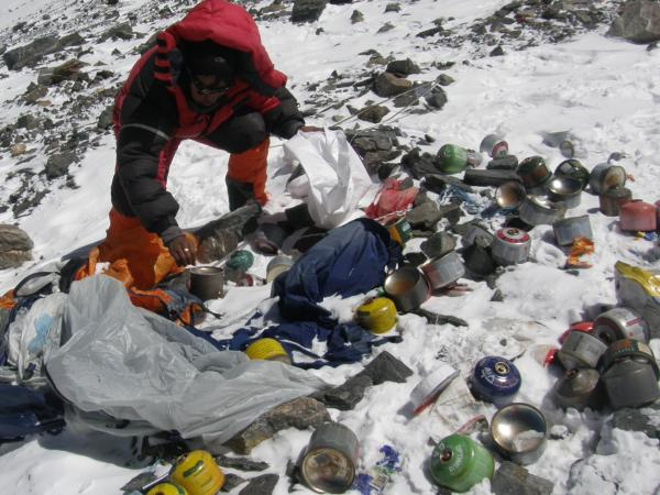 A Nepalese Sherpa collecting garbage, left by climbers, at an altitude of 26,250 feet during a special Everest clean-up expedition.
