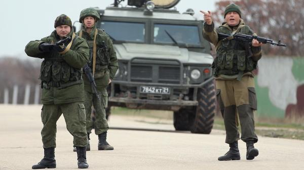 Troops under Russian command scream orders to turn back before firing warning shots at the Belbek airbase in Crimea. The troops were reacting to a large group of unarmed Ukrainian troops who approached them.