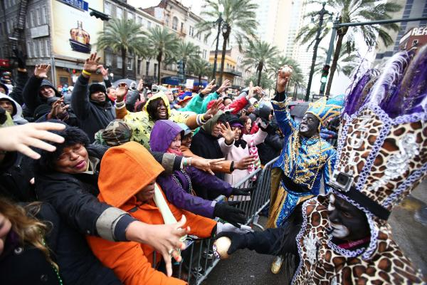 Participants of the Krewe of Zulu Parade hand out painted coconuts to spectators in New Orleans.