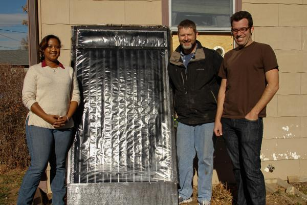 Metro State University students Zyola Mix and Richard Anderson stand with professor Aaron Brown next to solar furnace. (Jessica Taves/Metro State University)
