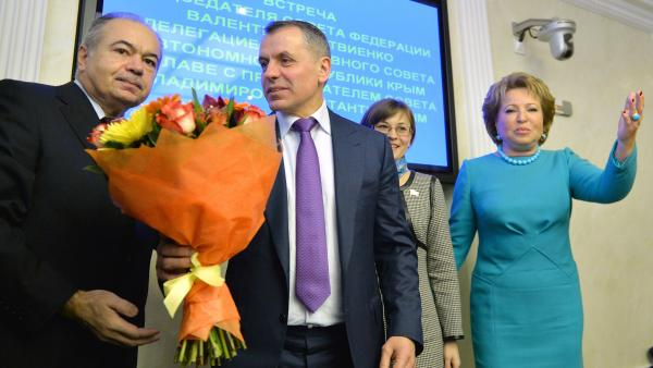 Vladimir Konstantinov (in purple tie) is the speaker of Crimea's parliament. He was welcomed with flowers Friday during his meeting with Valentina Matviyenko, speaker of Russia's upper house of parliament. She is at the far right of this photo.