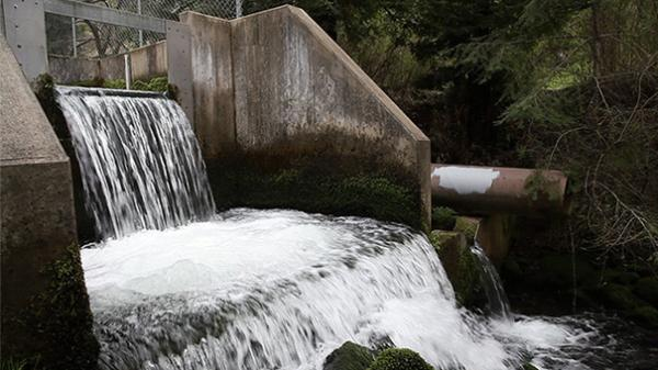 A steady cascade of water is released below Peters Dam in Marin County, Calif. Recent rainfall has improved conditions in parts of California, but the state remains in a drought.