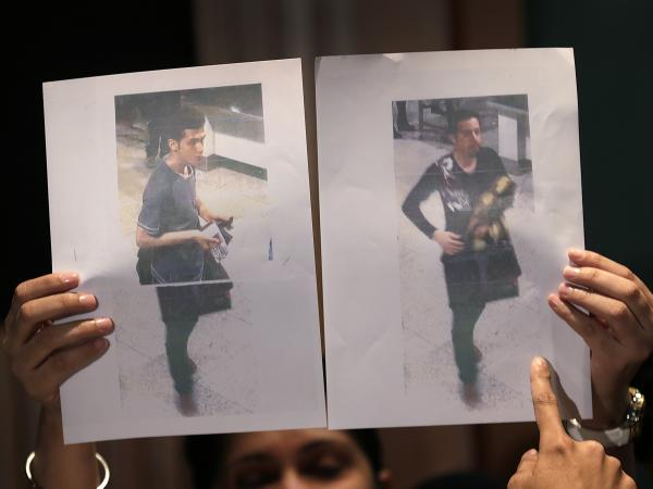 At a news conference Tuesday in Sepang, Malaysia, authorities held up pictures of the two Iranian men who are said to have boarded Malaysia Airlines Flight 370 with stolen passports. The man at left is said to 19-year old Pouria Nour Mohammad Mehrdad. The other man was not identified. Authorities believe the men were trying to emigrate to Europe.