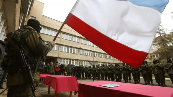 A masked man, believed to be a Russian soldier, holds a Crimean flag as members of a pro-Russian self-defense unit stand in formation Monday in the regional capital of Simferopol.