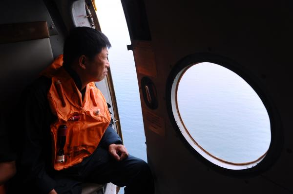 This picture taken aboard a Vietnamese Air Force Russian-made MI-171 helicopter shows a crew member looking out from a door during a search flight some 200 km over the southern Vietnamese waters off Vietnam's island Phu Quoc on March 11, 2014 as part of continued efforts aimed at finding traces of the missing Malaysia Airlines MH370. (Hoang Dinh Nam/AFP/Getty Images)