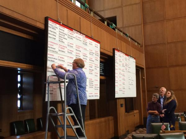 A state elections worker puts another name up on the board in the Oregon House showing candidates who have filed to run in the May 2014 primary.
