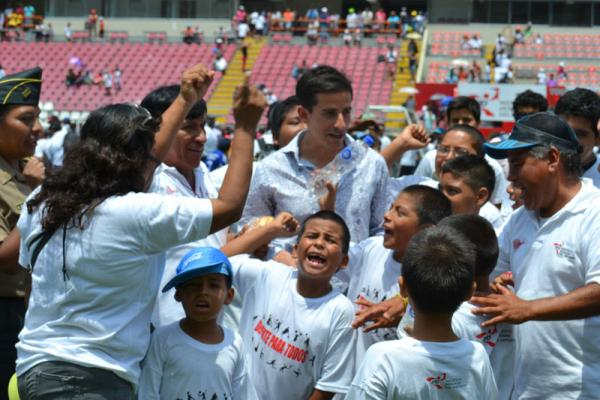 Peruvians surround Olympian Roberto Carcelen at the national soccer stadium in Lima after he delivered a pep talk.