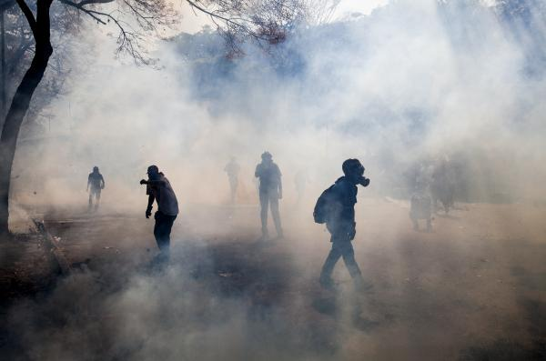 Demonstrators walk through a cloud of tear gas fired by the Bolivarian National Police during clashes in Caracas, Venezuela, on Wednesday.