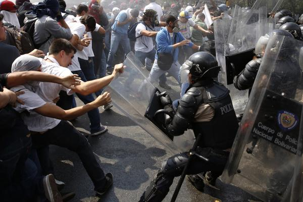 Anti-government protesters clash with police during a march that escalated into a street battle in the capital, Caracas, on Wednesday.