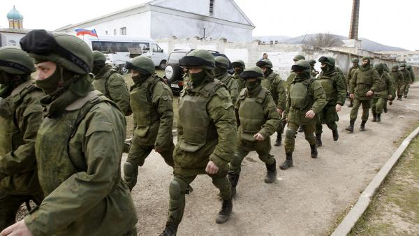 Armed men, believed to be Russian troops, walk outside a Ukrainian military base in Perevalnoye, near the Crimean city of Simferopol, on Friday.