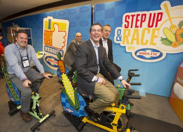 Birds Eye frozen vegetables executives Michael Barkley, Mark Schiller, Kristopher Corbin and Chef Michael Christensen race on veggie bikes at the PHA Building a Healthier Future Summit in Washington D.C., Mar. 13, 2014. (Johnny Bivera/Feature Photo Service for Bird's Eye)