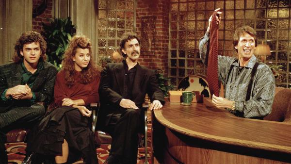 Comedian David Brenner, a staple of TV in the 1970s and '80s, has died at age 78. He's seen here hosting his <em>Nightlife </em>show, with<em> </em>musician Frank Zappa (center) and his children, Dweezil (left) and Moon Unit.
