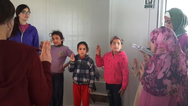 "An informal Girl Scout group at the Zaatari refugee camp in Jordan sings: ""We want to learn and rise up to fulfill our dreams."""