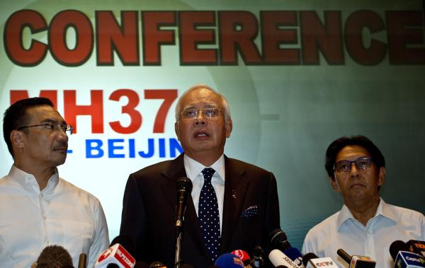 Malaysian Prime Minister Najib Razak addresses the media alongside Malaysia's Minister of Defence and Acting Transport Minister, Hishammuddin Hussein (left) and Director General of Civil Aviation Department, Azharuddin Abdul Rahman (right) during a press conference at a hotel near Kuala Lumpur International Airport in Sepang on March 15, 2014.  (Manan Vatsyayana/AFP/Getty Images)