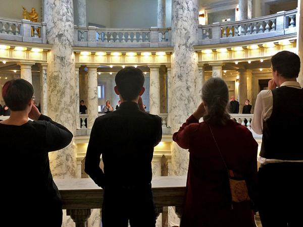 """Add the Words protesters encircle the upper level of the rotunda at the Idaho Capitol. They put a hand over their mouth to symbolize how they've been """"silenced"""" by lawmakers."""