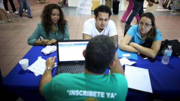 Ashante Thurston, John Riascos and Julieth Riascos talk with Mario Ricart, a private insurance agent, about buying health insurance at a kiosk at the Mall of the Americas in Miami last year.
