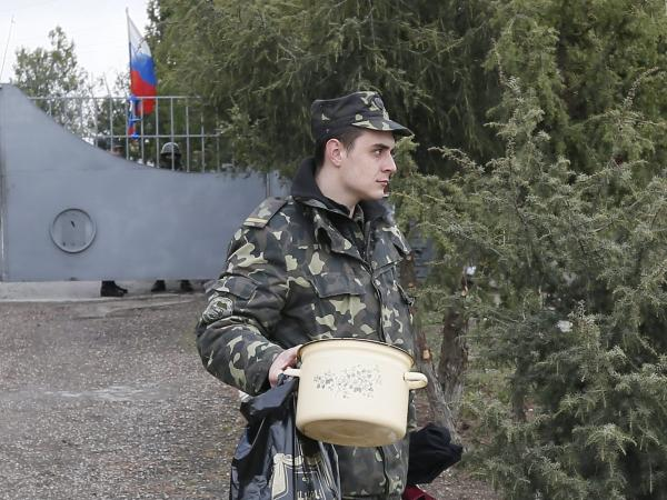 "A Russian flag flies behind him Thursday as a Ukrainian soldier leaves what was one of his military's bases outside Simferopol, on the Crimean Peninsula. Local ""self-defense forces,"" followed by Russian troops, have seized many strategic locations."