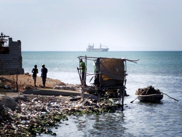 A makeshift latrine hangs over the water at the edge of Cite de Dieu, a slum in Port-au-Prince, Haiti.