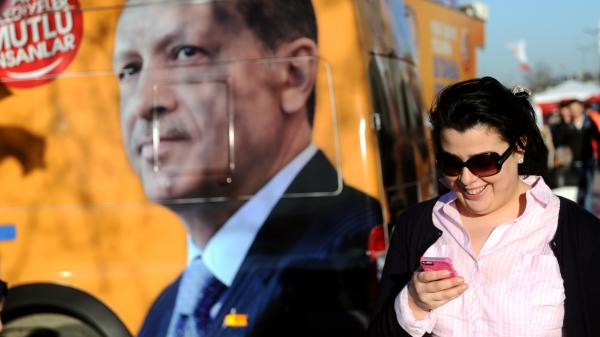 A woman looks at her smartphone as she walks by a banner of Turkish prime minister Recep Tayyip Erdogan, in Istanbul on March 21. On Thursday, Turkish court orders banned Internet users from accessing Twitter, but the social media company posted instructions on how to tweet from a phone.