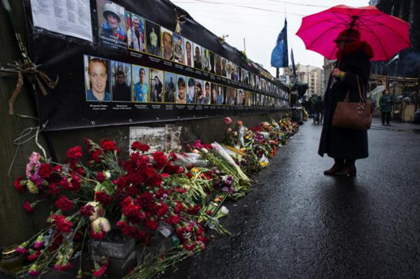 The faces of people killed in Independence Square is memorialized on a wall in Kiev, Ukraine. The Ukrainian government has promised justice for the fallen, but citizens in Kiev remain uneasy. (Nikki Kahn/The Washington Post via Getty Images)