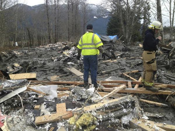 Officials survey a large mudslide in this handout photo provided by the Washington State Police near Oso, Washington on Sunday.