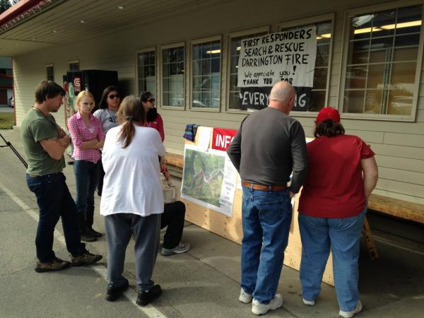 Darrington residents gather outside town grocery store for word of missing. (Phyllis Fletcher/KUOW)