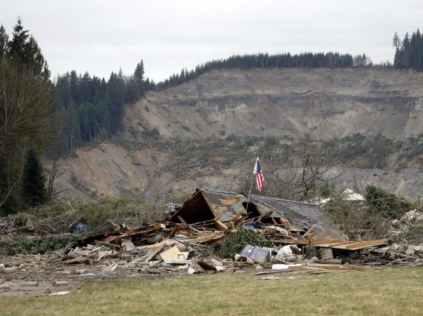 A flag, put up by volunteers helping search the area, stands in the ruins of a home left at the end of a deadly mudslide from the now-barren hillside in Oso, Wash., on Tuesday.