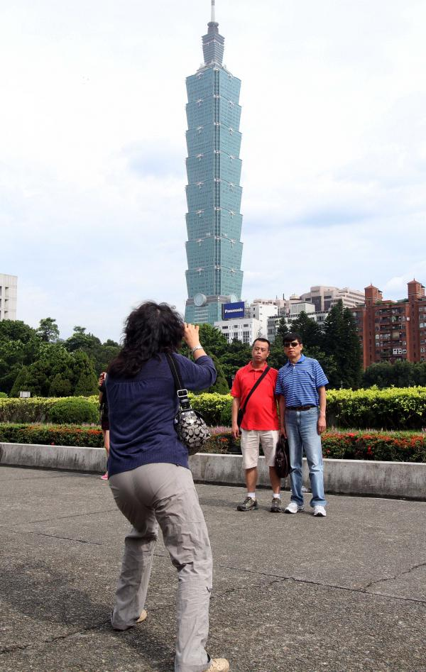 Chinese tourists take photos in front of the Taipei 101 building from the grounds of the Sun Yat-sen memorial hall in Taipei in June 2011. Nearly 3 million tourists from mainland China visited Taiwan last year, up from just 300,000 in 2007.