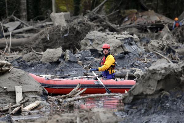 A searcher uses a small boat to look through debris in Oso. <em>The Seattle Times</em> reports that geological studies have warned for decades that the area of Snohomish County where Oso is located was at risk for landslides.