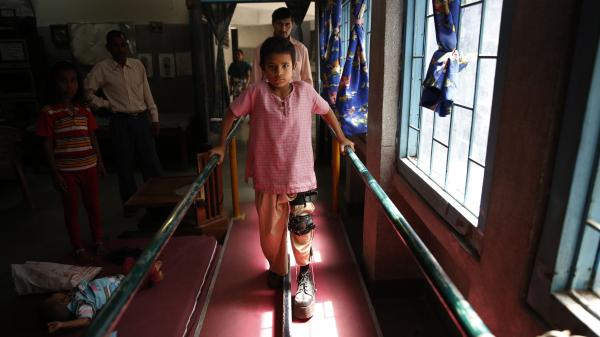 Eight-year-old Manish, who caught polio years ago, learns to walk with leg braces at a rehabilitation center in New Delhi on Thursday.