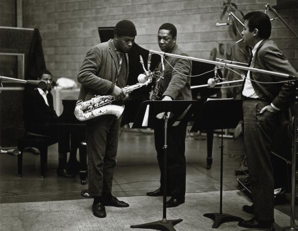 "Coltrane (center right) discusses a passage of <em>A Love Supreme</em> with producer Bob Thiele (right), saxophonist Archie Shepp (center left) and pianist McCoy Tyner. Shepp played on the alternate take of the first movement, ""Acknowledgement."""