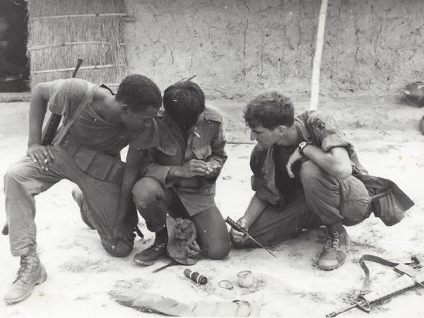 In this photo from 1969, Leon Strigotte (far right) examines a disarmed boobytrap. Strigotte served in an airborne infantry unit and lead a recon team during his second tour of duty in Vietnam in 1969.