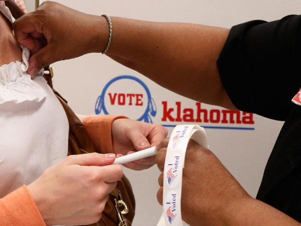 "Election board  inspector Pat Cook places an ""I Voted"" sticker on a voter during early voting in Oklahoma City late last month."