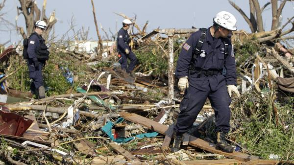 Oklahoma Task Force One search-and-rescue members (from left) Jim Winham, Nick Swainston and Kevin Mann search through debris for victims Tuesday in Joplin, Mo.
