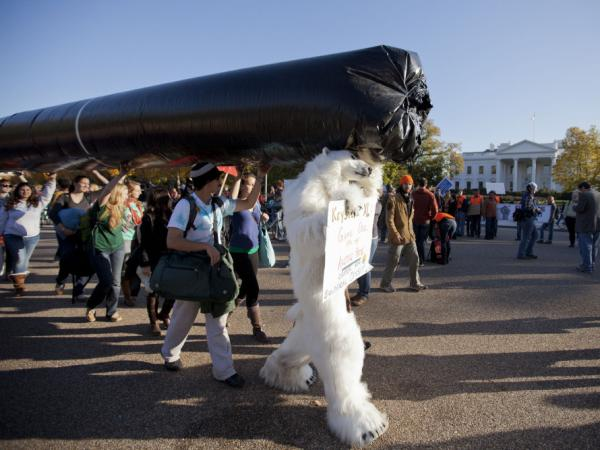 Demonstrators march with a replica of a pipeline during a protest to demand a stop to the Keystone XL tar sands oil pipeline outside the White House last November.