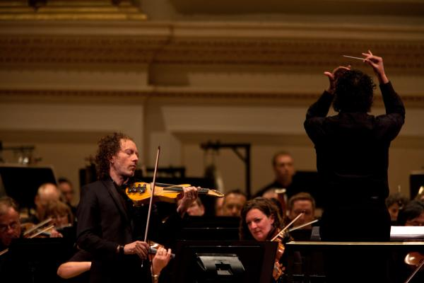 The concert also featured the New York premiere of Terry Riley's <em>The Palmian Chord Ryddle for Electric Violin and Orchestra</em>, a piece he wrote for the soloist, Tracy Silverman. Silverman designed his own six-string instrument that reaches down into the cello range.