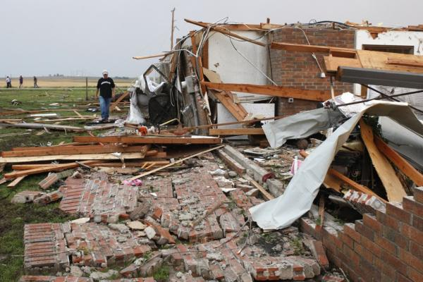 Matt McElvany walks past the home of a friend in Piedmont, Okla., following a tornado on Tuesday.