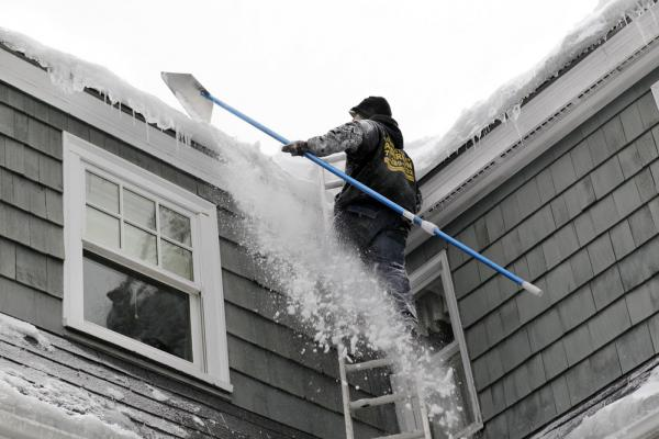 Andrew Santino of Santino's Roofing uses a rake to clear snow from a residential roof in Andover, Mass., on Wednesday.